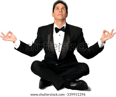 Caucasian man with short black hair in a tuxedo with meditation hands - Isolated - stock photo