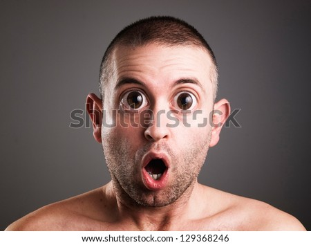 Caucasian man with surprised expression. The man is looking at camera and is isolated on black background. - stock photo