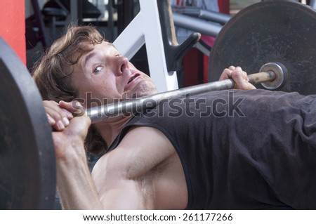Caucasian man working out in gym is stuck under heavy barbell on bench press - stock photo