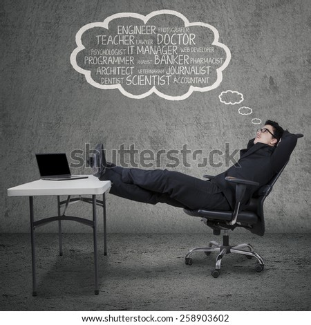 Caucasian manager in formal suit, sitting on chair while dreaming his future jobs - stock photo