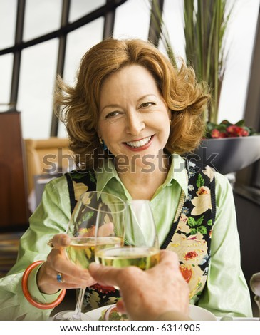 Caucasian mature couple toasting with white wine in restaurant.
