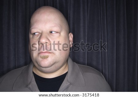 Caucasian mid adult bald man looking to side.