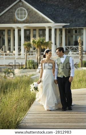 Caucasian mid-adult bride and groom walking down wooden beach walkway holding hands.
