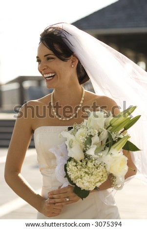 Caucasian mid-adult bride holding flower bouquet and smiling.
