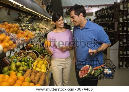 Caucasian mid-adult couple grocery shopping for fruit.