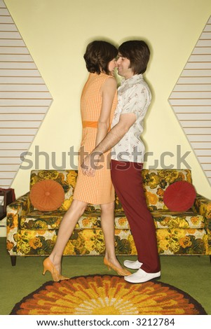 Caucasian mid-adult couple wearing vintage clothing standing close holding hands with noses touching. - stock photo
