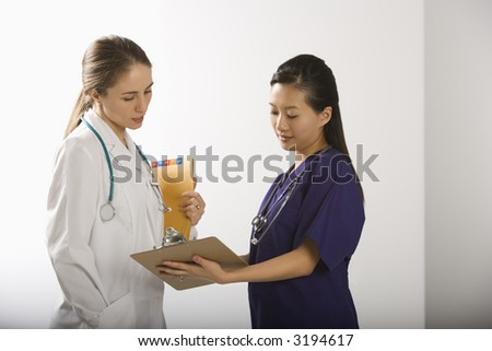 Caucasian mid-adult female doctor and Asian Chinese mid-adult female physician's assistant discussing paperwork. - stock photo