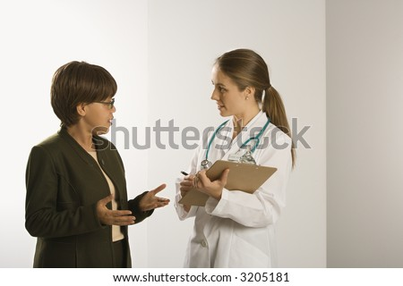 Caucasian mid-adult female doctor talking with African American middle-aged female patient. - stock photo
