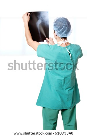 Caucasian mid adult male doctor holding up xrays. - stock photo
