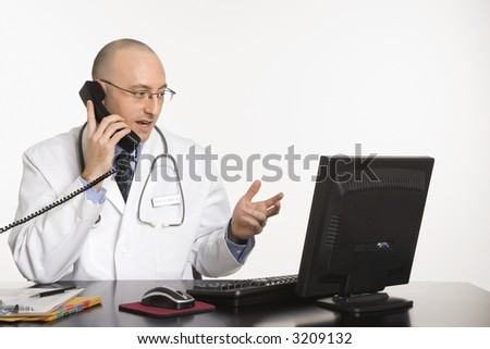 Caucasian mid adult male physician sitting at desk with laptop computer talking on telephone. - stock photo