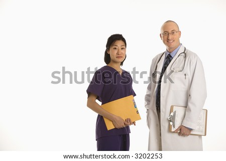 Caucasian mid adult male physician with Asian woman doctor. - stock photo