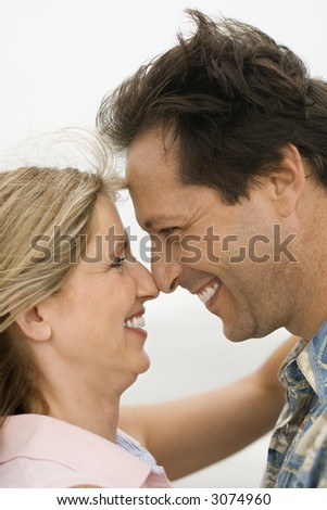 Caucasian mid-adult man and woman holding each other and looking into each other's eyes on beach.