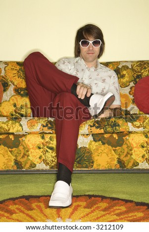 Caucasian mid-adult man sitting on colorful retro sofa wearing sunglasses looking bored. - stock photo
