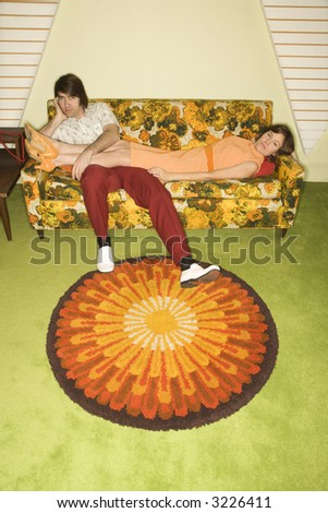 Caucasian mid-adult woman lying on colorful retro sofa with legs draped over Caucasian mid-adult man. - stock photo