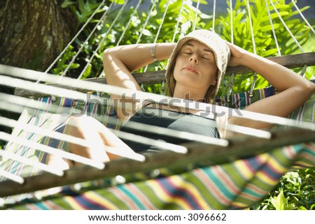 Caucasian mid-adult woman napping in hammock. - stock photo