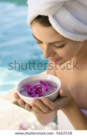 Caucasian mid-adult woman wearing towel around head and body holding bowl of purple orchids next to pool.