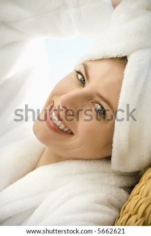 Caucasian mid-adult woman wearing towel on head smiling at viewer.