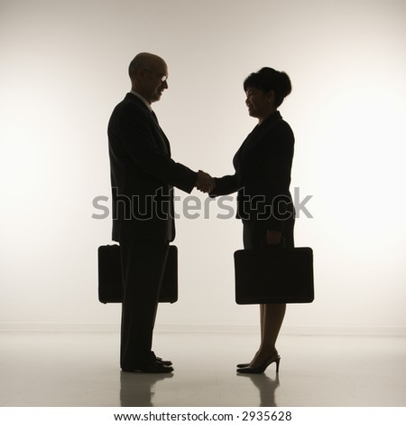 Caucasian middle-aged businessman and Filipino businesswoman standing looking at eachother shaking hands against white background.