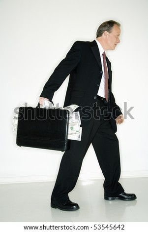 Caucasian middle aged businessman carrying briefcase overflowing with money. - stock photo