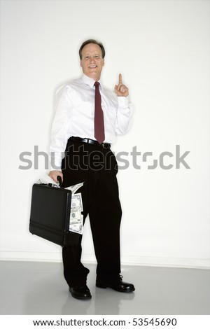 Caucasian middle aged businessman carrying briefcase overflowing with money holding up one finger. - stock photo