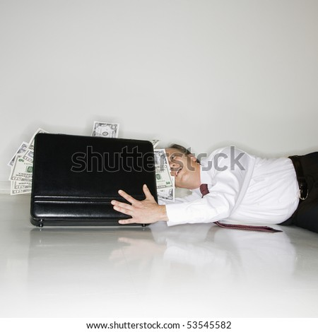 Caucasian middle aged businessman grabbing at briefcase overflowing with money. - stock photo