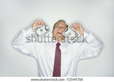 Caucasian middle aged businessman holding hudred dollar bill ripped in half laughing. - stock photo
