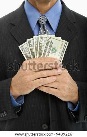Caucasian middle aged businessman holding several twenty dollar bills.