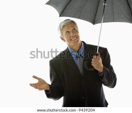 Caucasian middle aged businessman holding umbrella and gesturing. - stock photo