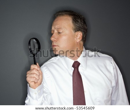 Caucasian middle aged businessman looking through magnifying glass. - stock photo