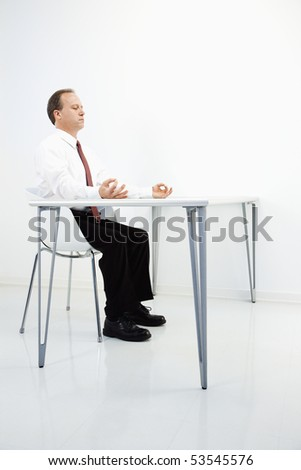 Caucasian middle aged businessman sitting at desk meditating. - stock photo