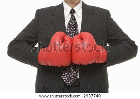 Caucasian middle-aged businessman wearing boxing gloves - stock photo