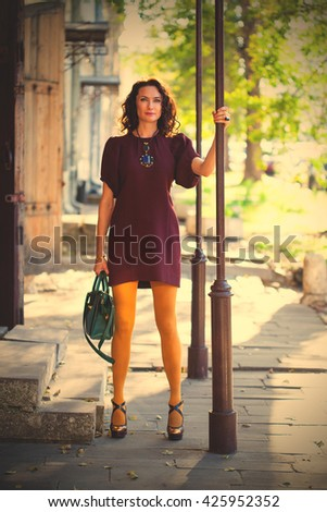 Caucasian middle-aged woman in a fashion burgundy dress, style mustard-colored tights and a green hand-bagin hand on an old street near the old porch. instagram image filter retro style - stock photo