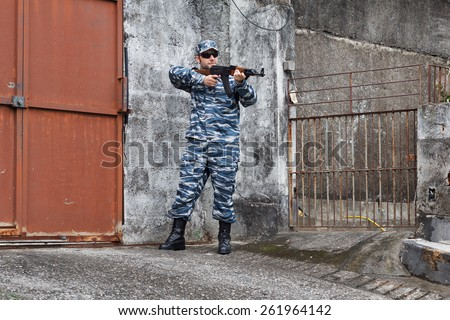 Caucasian military man with black sunglasses in urban warfare protecting iron gate with rifle - stock photo