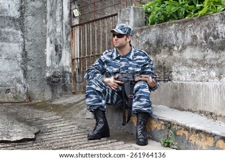 Caucasian military man with black sunglasses in urban warfare sitting with automatic weapon