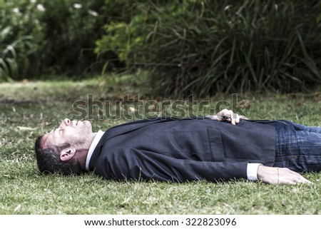 Caucasian modern businessman with grey suit and jeans lying on grass sleeping and relaxing in city park to think and enjoy lunchtime, profile view in daylight with dramatic contrast effect - stock photo