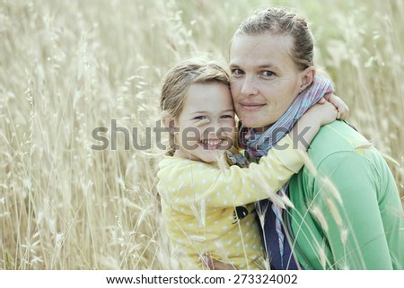 Caucasian mother and daughter hugging, smiling and sharing a tender bonding moment amongst meadow grass. Mothers day concept. Serenity and tranquility. Desaturated vintage look.  - stock photo