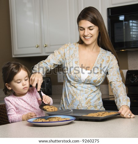Caucasian mother and daughter  with cookies. - stock photo