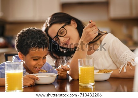 caucasian mother and mixed race african son eating breakfast together