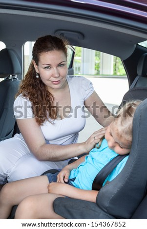 Caucasian mother caressing her daughter sleeping in the car seat safety - stock photo