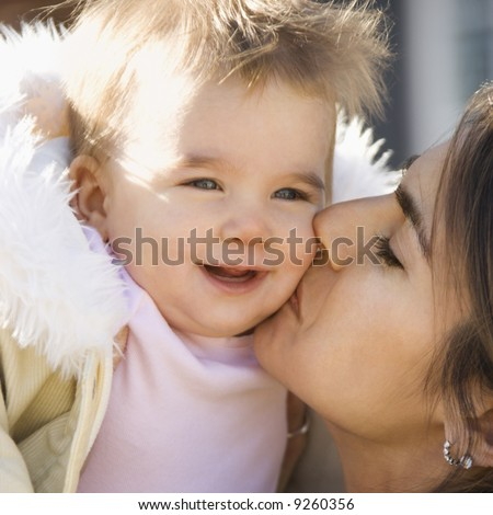 Caucasian mother holding and kissing smiling baby girl. - stock photo
