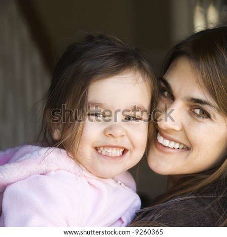 Caucasian mother holding daughter and smiling. - stock photo