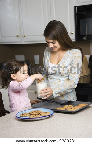 Caucasian mother holding milk glass while daughter dunks cookie. - stock photo