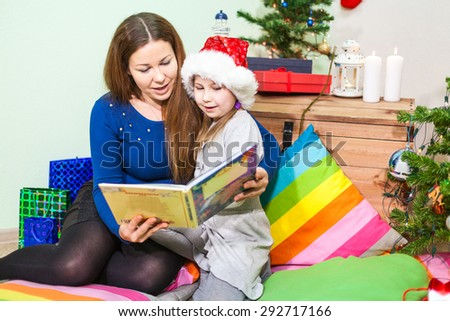 Caucasian mother reading the book daughter near green tree at the night before the Christmas - stock photo