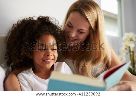 Caucasian mum and smiling black daughter read in bed, close-up - stock photo