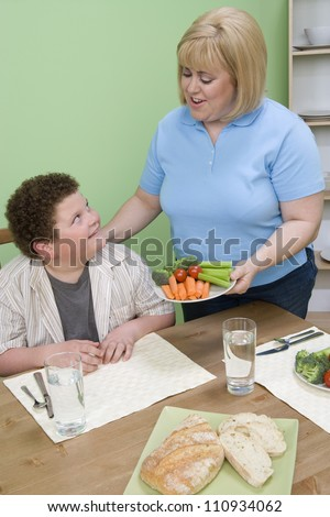 Caucasian obese mother and son having meal together at home