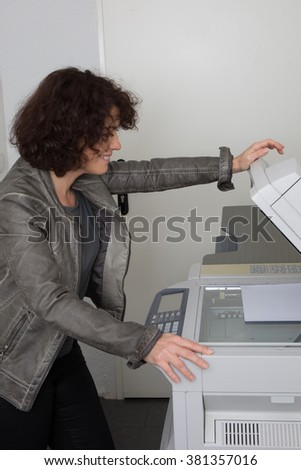 Caucasian office woman lifting up lid of copy machine at work - stock photo