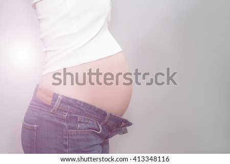 caucasian pregnant girl in unbuttoned jeans and a white t-shirt holding on to naked belly in the studio on a gray background