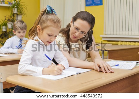 Caucasian primary school teacher and pupil sitting at a desk. Girl writes in a notebook. The teacher looks at her and smiles. Horizontal color image.