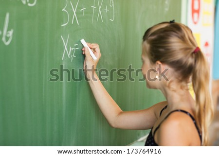 Caucasian schoolgirl solving an equation on the blackboard. - stock photo
