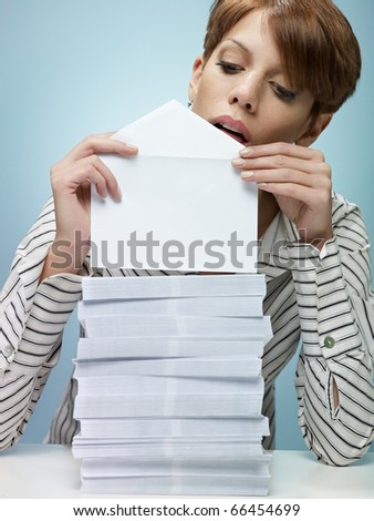caucasian secretary closing pile of envelopes. Vertical shape, front view, waist up, copy space